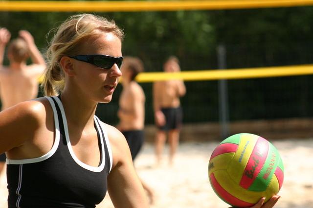blondýnka s culíkem a černými brýlemi na očích v černobílém tričku má barevný balón a hraje volejbal
