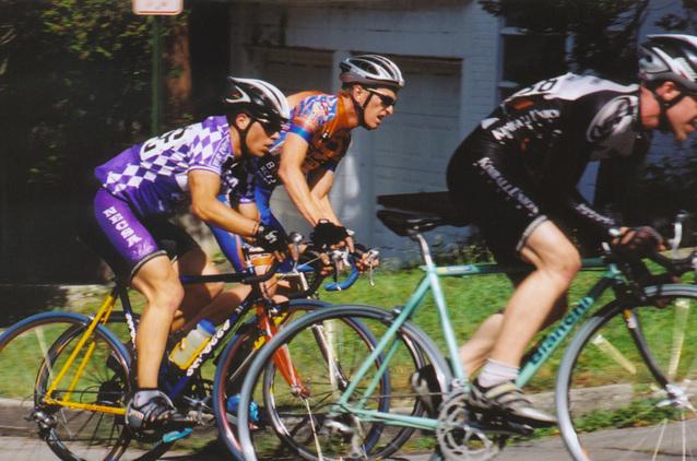 tři závodníci jedou na kole, ve fialovém dresu, v oranžovém a v černém