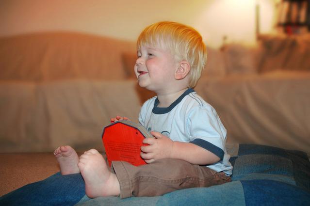dítě sedící na velkém modrém polštáři s blonďatými vlasy