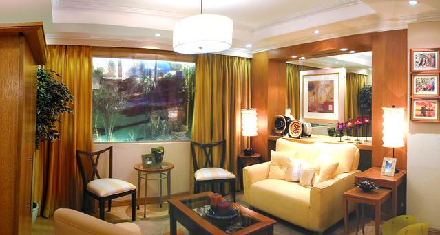 obývací pokoj se světlým křeslem, židlemi, stoly, obrazy a svíčkami