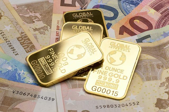 peníze a na nich čtyři zlaté cihličky
