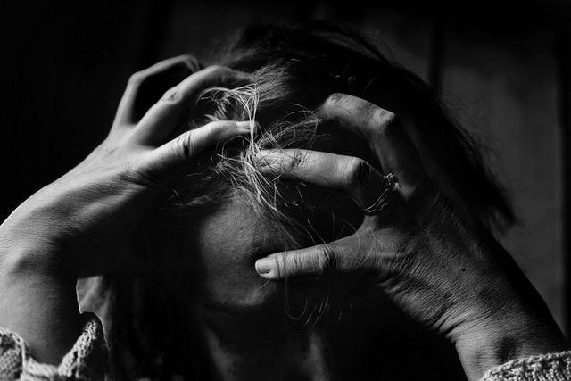 žena držící se za hlavu