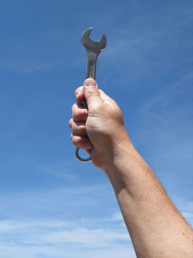 ruka držící klíč vzhůru k nebesům
