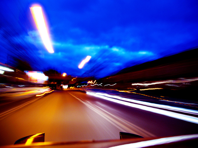Pohled z automobilu rychlá jízda, rozmazaná vozovka, světla ve tmě
