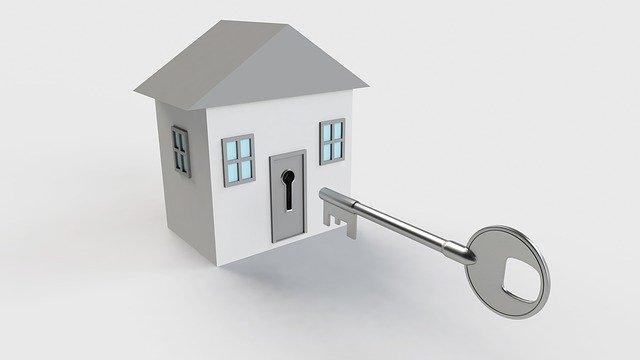klíč a model domu v šedé