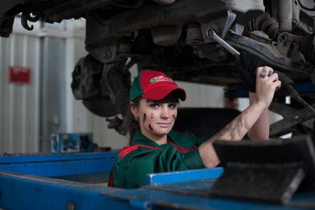 mladá dívka opravující auto v dílně