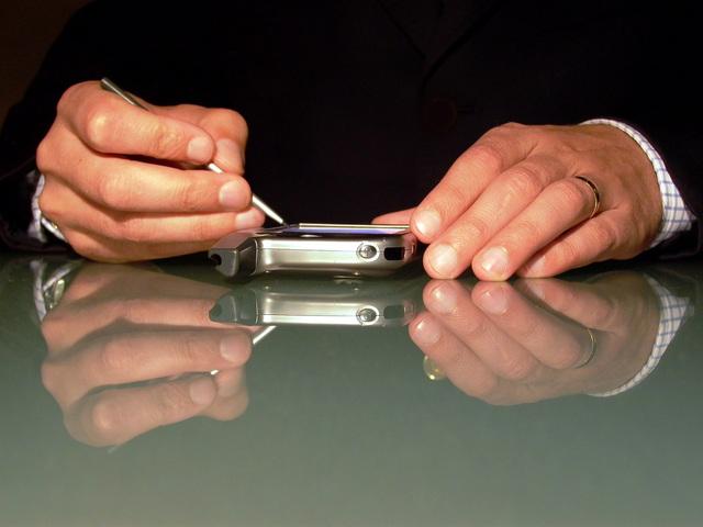 na skleněném stole je položený telefon