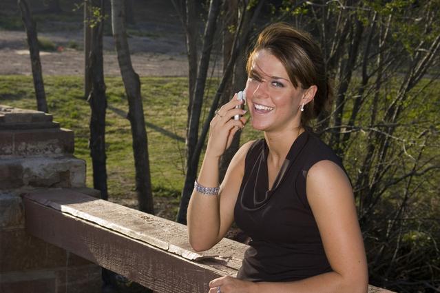 dívka sedí někde u parku u zábradlí a telefonuje