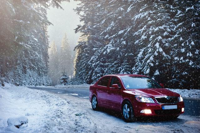 automobil v zimě na silnici v lese