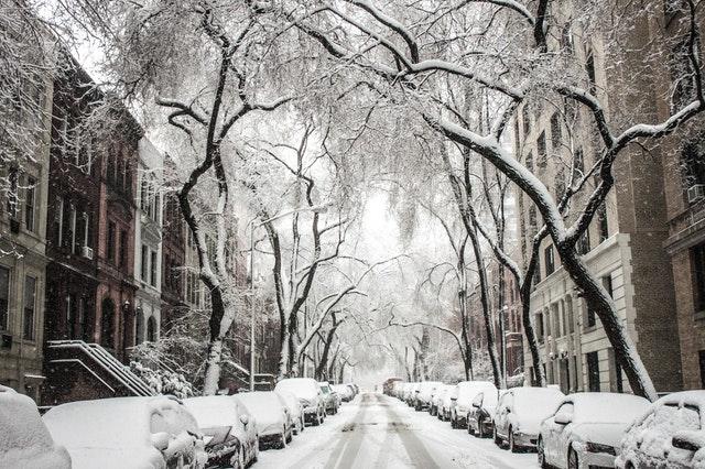ulice se zaparkovanými auty pod sněhem